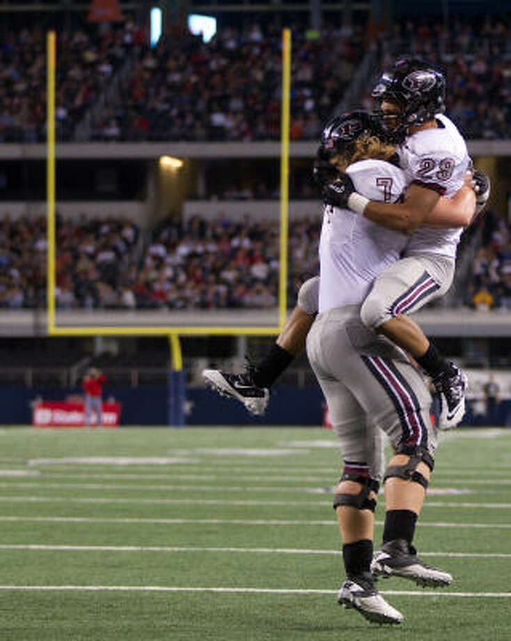 Pearland running back Dustin Garrison (29) celebrates with offensive linesman Kyle Mulligan (74) after scoring a touchdown during the first half on Saturday night at Cowboys Stadium. Photo: Smiley N. Pool, Chronicle