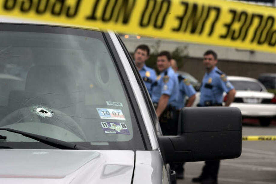 A group of HPD officers stand behind a Ford F-150 truck that had been shot at during a gunfight near the intersection of the Southwest Freeway and Bissonnet on Tuesday. Photo: Johnny Hanson, For The Chronicle