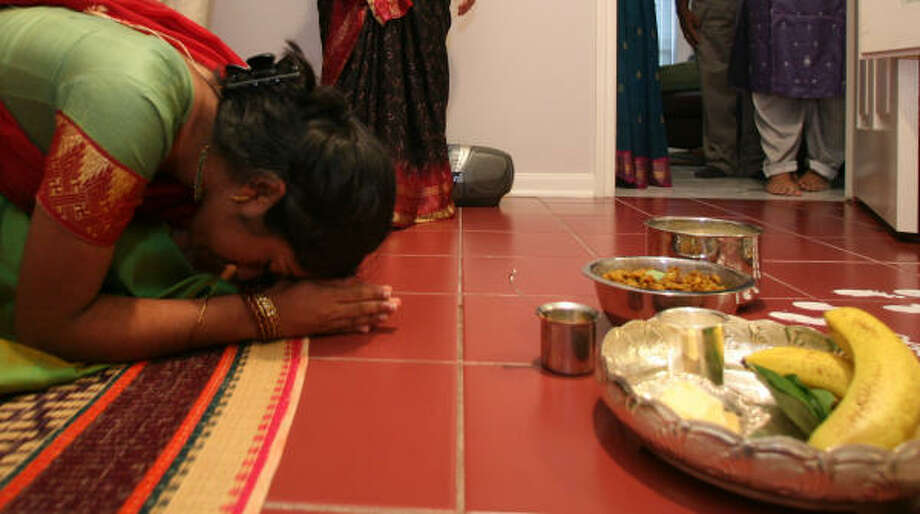 KEEPING TRADITION:Latha Ramdas' daughter, Deepa, 17, prays to and salutes Lord Krishna in her family's prayer room, which is what they plan to do for Janmashtami on Tuesday. Photo: Steve Campbell, Chronicle