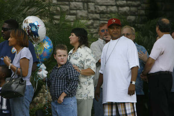 Mark Davis, 8, with his mother, Elisa, waits in line with balloons at the visitation for Channel 13 consumer advocate Marvin Zindler, who died Sunday. He would have turned 86 on Aug. 10.