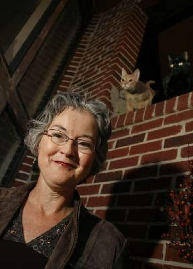 She may be an erudite philosophy professor in the daylight hours, but like everyone else, Cynthia Freeland — with feline friends Sampson, left, and Cleo — gets creeped out herself once in a while. Photo: STEVE UECKERT, CHRONICLE