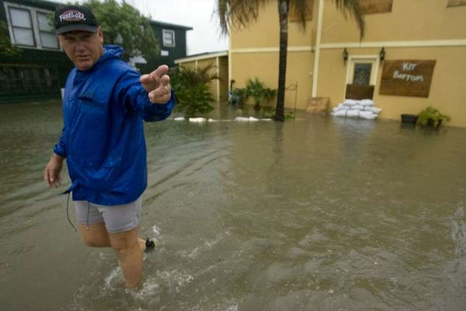 Gilchrist resident Ricky Tribble walks Tuesday from his Bolivar Peninsula home, flooded with a foot of water by Edouard. Photo: JOHNNY HANSON, CHRONICLE