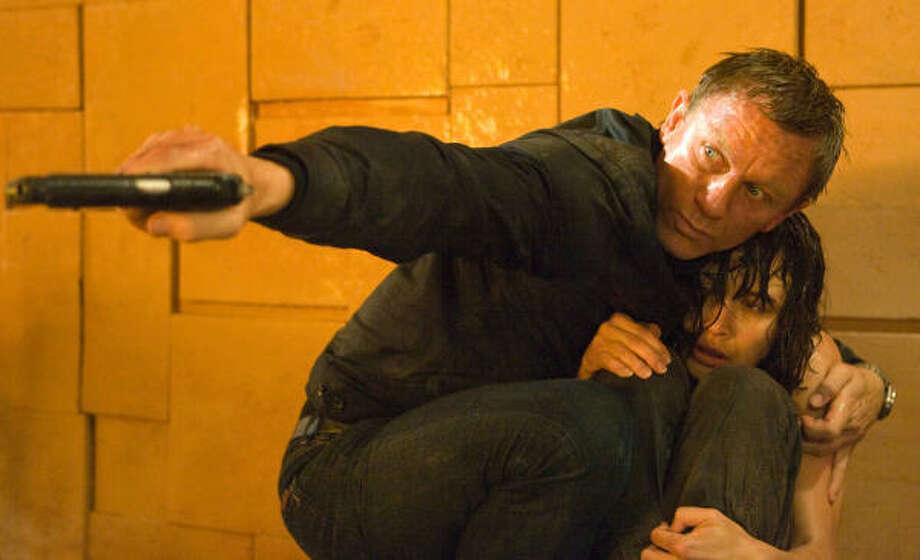 OUT FOR VENGEANCE: James Bond (Daniel Craig) shields Camille (Olga Kurylenko) in a scene from Quantum of Solace. The 22nd Bond movie picks up where 2006\u2019s Casino Royale left off as Agent 007 looks to avenge Vesper Lynd\u2019s death. Photo: Karen Ballard