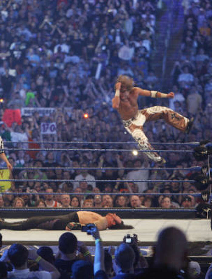 Shawn Michaels, right, goes airborne as he slams on top of the Undertaker during one of the main events at the 25th anniversary of Wrestlemania on Sunday at Reliant Stadium. Photo: Julio Cortez, Chronicle