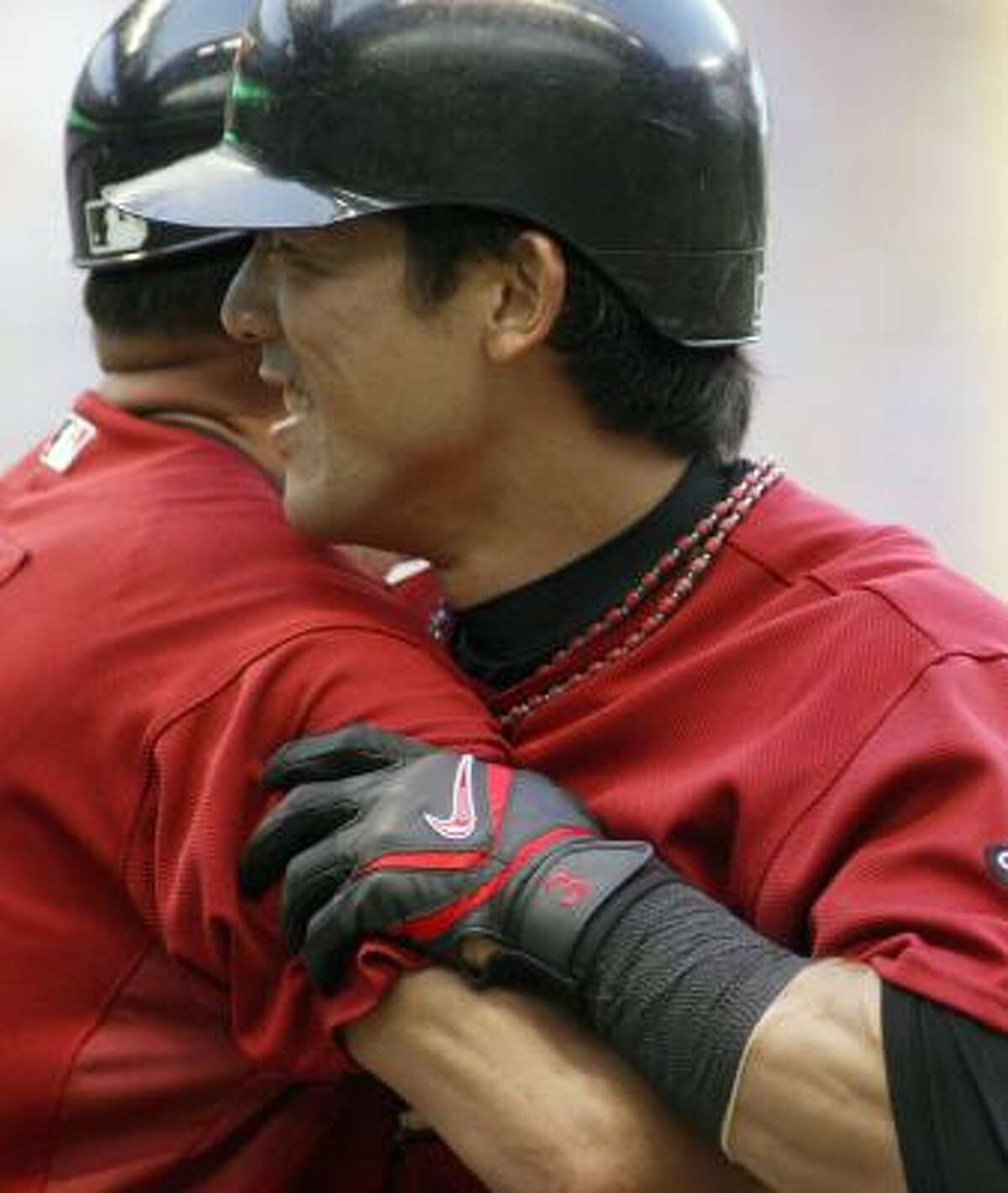 Kaz Matsui, right, is congratulated by first base coach Jose Cruz after career hit number 2,000 during the third inning against the Milwaukee Brewers on Saturday. Matsui had 1433 hits while playing in Japan and 567 hits with the majors.