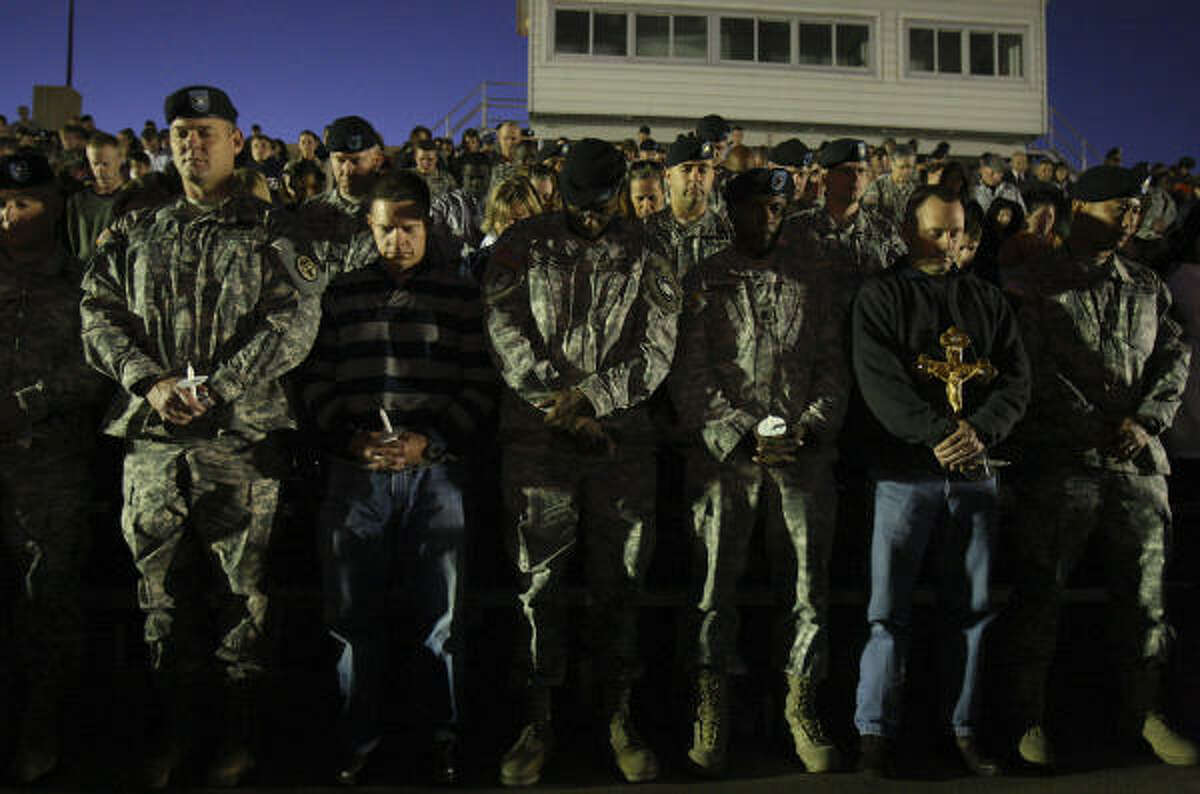 People pray during a candlelight vigil held at Hood Stadium on Friday.