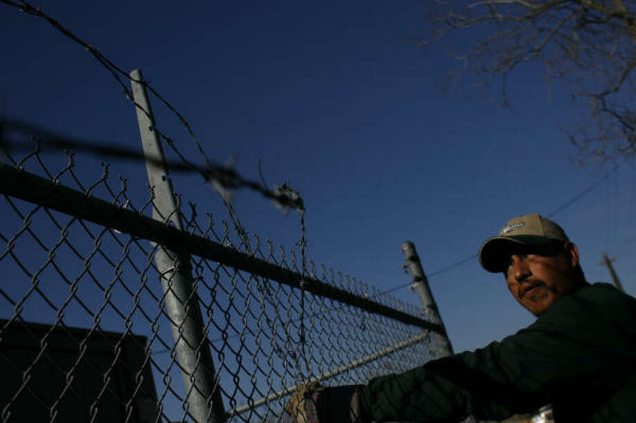 Thick gloves and stout clippers are all Roberto Rodriguez, with Fence Master Houston, needed Thursday to remove the final strands of barbed wire surrounding HISD's Emmett J. Scott Elementary. Photo: Johnny Hanson, Chronicle