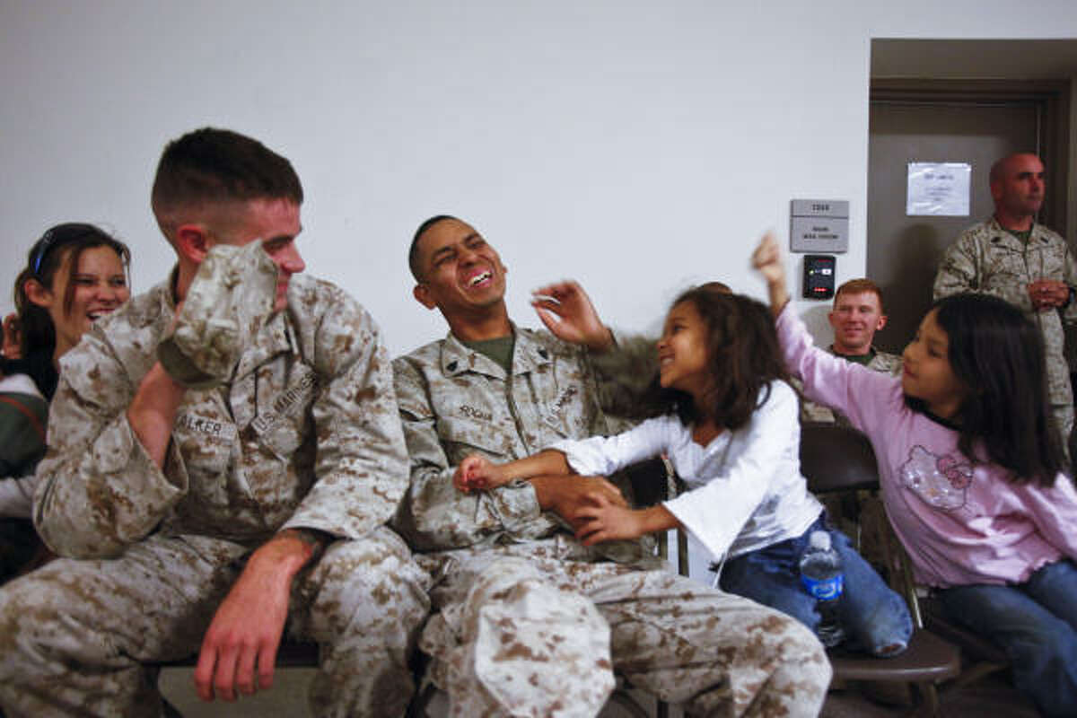 Marine Arnulfo Rocha is attacked by daughters Jenna, 6, and Lillee, 8, to the amusement of his wife, Wendy, and Marine Anthony Walker at the Armed Forces Reserve Center at Ellington Field.