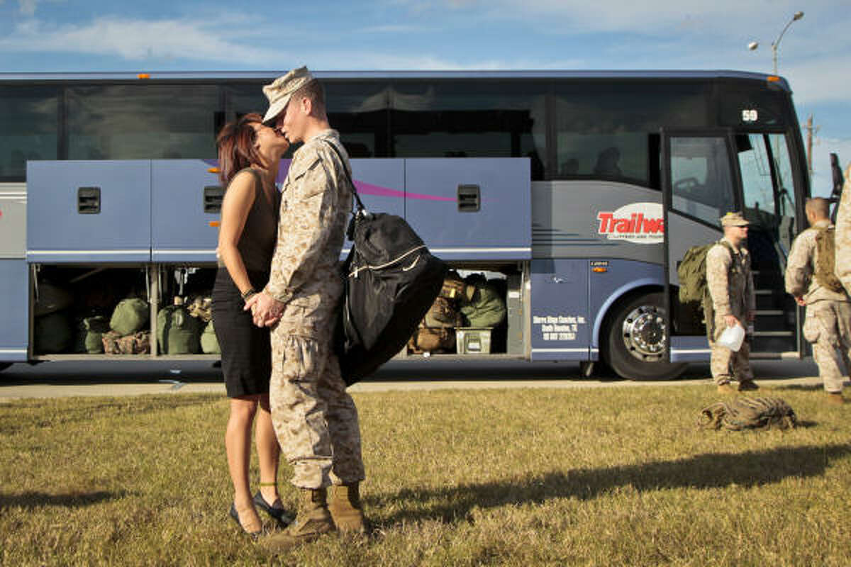 Marine Cpl. Erik Bjelke kisses his girlfriend, Felicia Lam, before boarding a bus Tuesday at Ellington Field for pre-deployment training at Camp Pendleton in California.