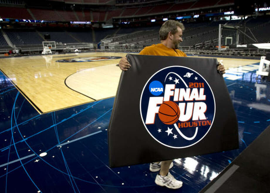 Billy Holt carries a backboard pad across the court at Reliant Stadium while putting the finishing touches on the playing surface for the Final Four on Monday. Photo: Brett Coomer, Chronicle