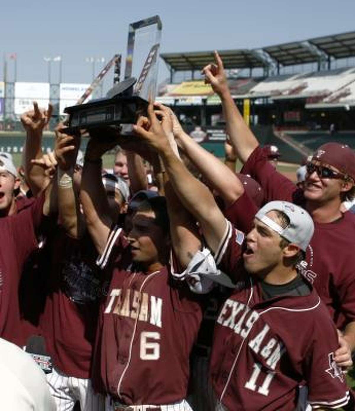 A&M's Andrew Collazo, center, holds the Big 12 Trophy and celebrates with his team after defeating Missouri in the Big 12 tournament title game on Sunday in Oklahoma City.