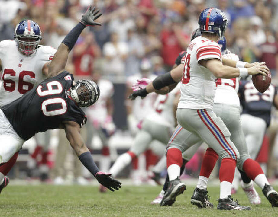 A horizontal Texans defensive end Mario Williams (90) tries to get to Giants quarterback Eli Manning (10) in the third quarter Sunday. Williams had three tackles but did not get to Manning, who was not sacked in the game. Photo: Karen Warren, Chronicle
