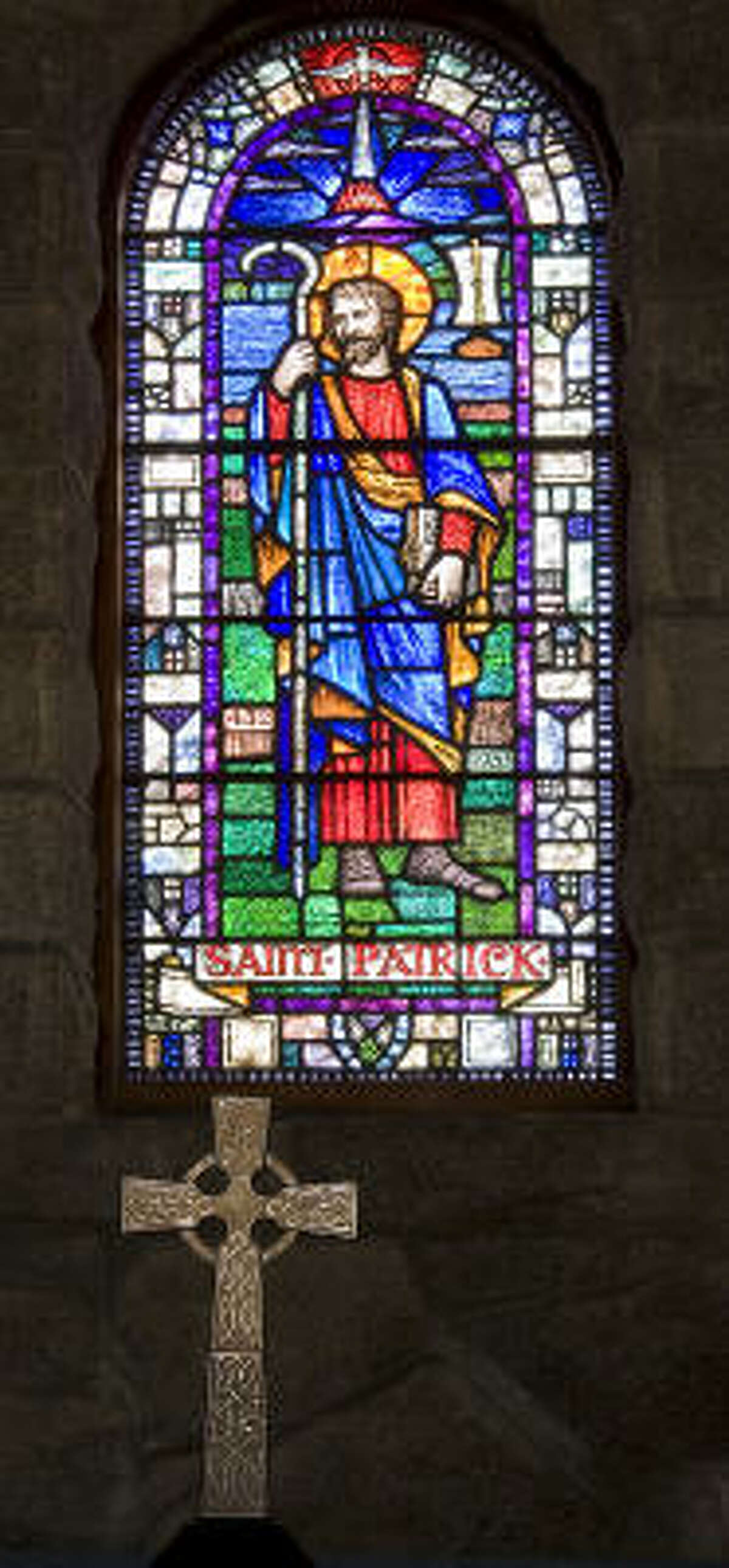 A stained glass window of saint patrick with celtic cross in foreground.