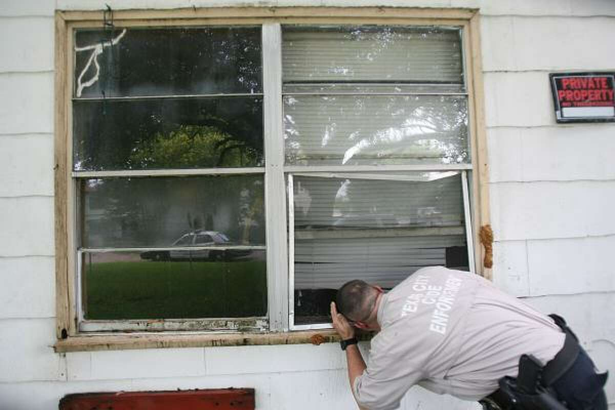 Texas City Code Enforcement Officer Cpl. Derrick Grandstaff peeks through a window of a condemned house Tuesday and discovers someone may be living there.