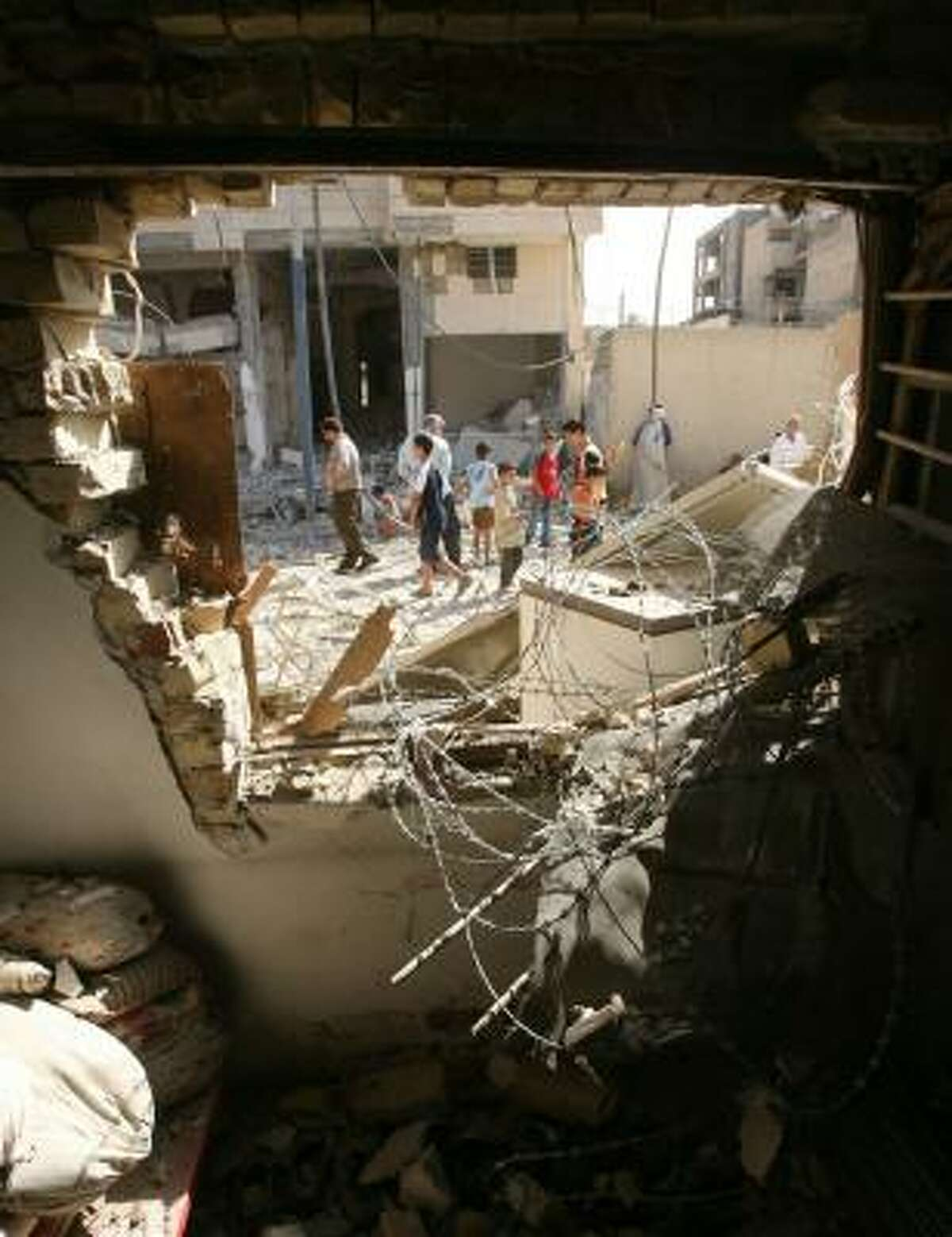 Framed by a hole in a building, Iraqis walk Thursday through rubble left from an overnight raid by U.S. troops in the Azamiyah neighborhood of Baghdad.
