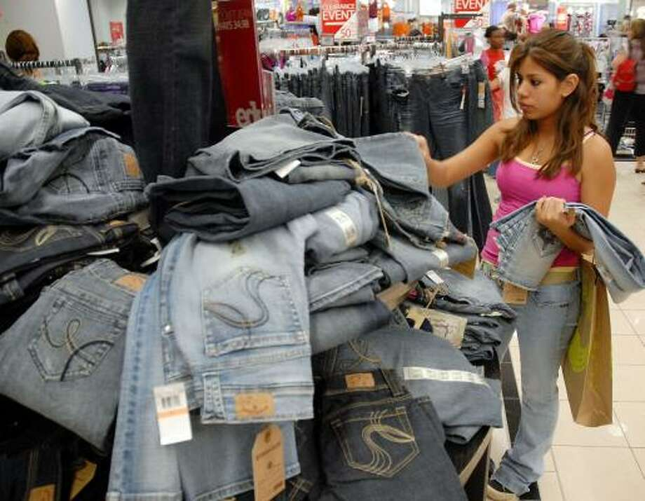Kempner High School student Dulce Surugui, 16, rifles through a pile of jeans at Macy's during tax-free weekend. Photo: Dave Rossman, For The Chronicle