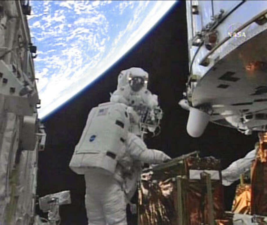 In this image from NASA TV with earth in the background astronauts John Grunsfeld, rear, and Andrew Feustel work to upgrade the Hubble Space Telescope, which was put into operation in 1988. Photo: AP