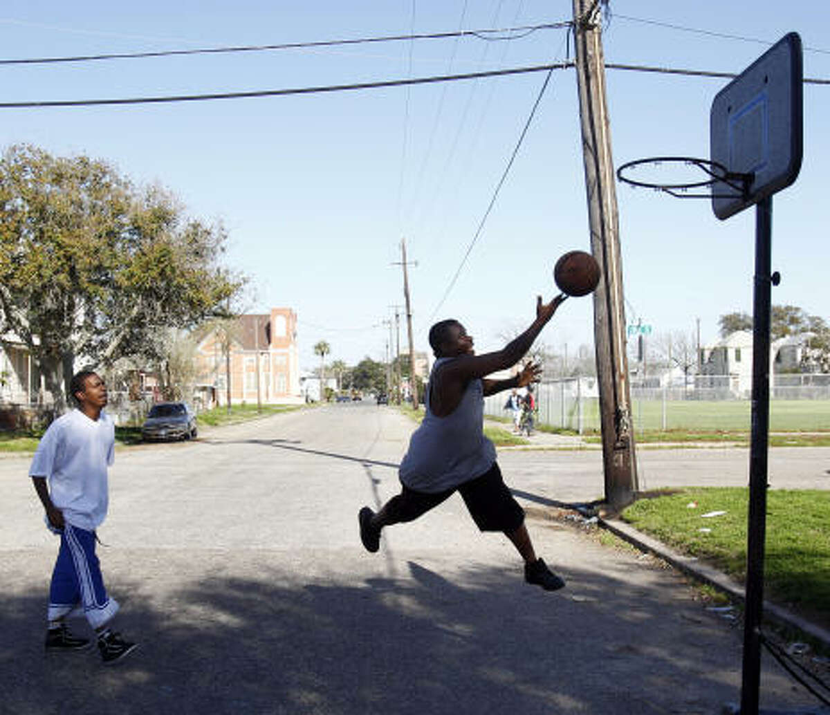 Robert Allen, left, and Mister Bates play basketball down the street from the Avenue L Missionary Baptist Church, the oldest black church in Texas. The black population of the Island dropped sharply in the first decade of the new century.