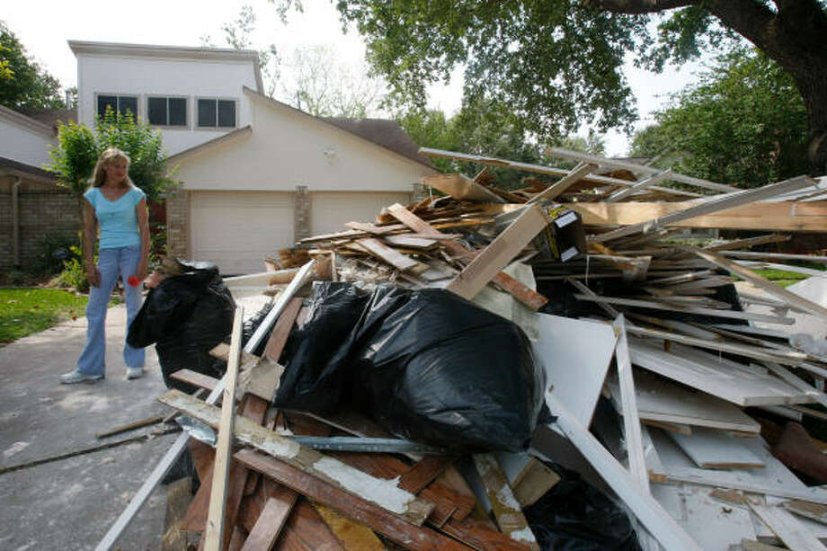 Jennifer Bayles, whose northwest Harris County home flooded in torrential downpours in late April, surveys the debris from a neighbor's home. Photo: Julio Cortez, Chronicle