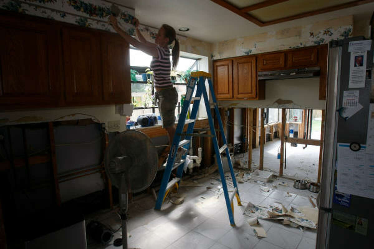 """Kathleen Sheldon, of Earthquest Interiors by LJL, pulls off wallpaper in the kitchen of Dan Rayne's house in Bear Creek, which was damaged by the heavy floods of April 27 and 28. Rayne, who fled with his two daughters to an upstairs loft as the waters rose, said, """"I pretty much lost my whole downstairs."""""""