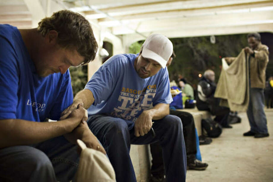 "Bobby ""Tre9"" Herring, center, prays with John Bradley who had been on the streets for 41/2 months after his roommate lost his job and created financial stress during Feed a Friend anniversary event, Nov. 12, 2010, in Houston, under the Main Street bridge near downtown. Photo: Eric Kayne, For The Chronicle"