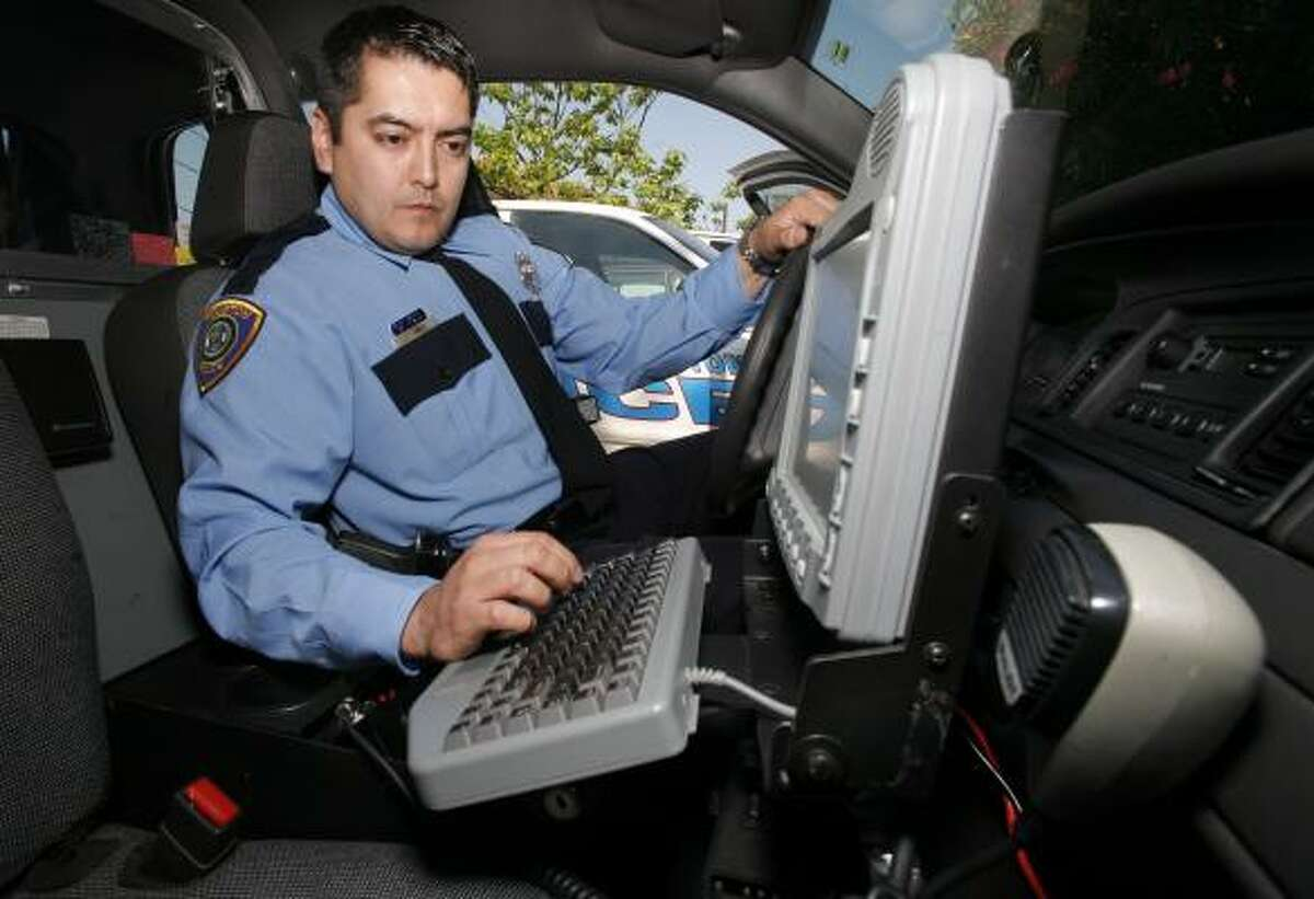 Officer Gabe Ortiz, a 10-year veteran of the Houston Police Department, demonstrates wireless technology available out on patrol.