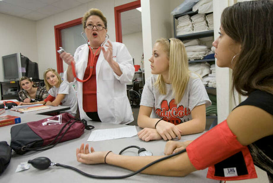 Splendora High School health and science technology teacher Nancy Mahlstadt, who is a registered nurse, teaches techniques for using a stethoscope to students, from left, Lauren Dorman, Danielle Plate, Taylor Stephens and Nikolle Cabrera.     Photo: Steve Campbell, Houston Chronicle