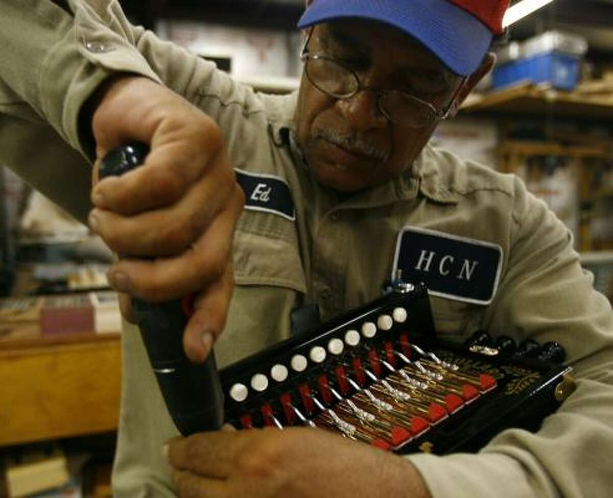 Ed Poullard puts the keyboard back on a finished accordion. He is thought to be the first Creole to learn the craft.
