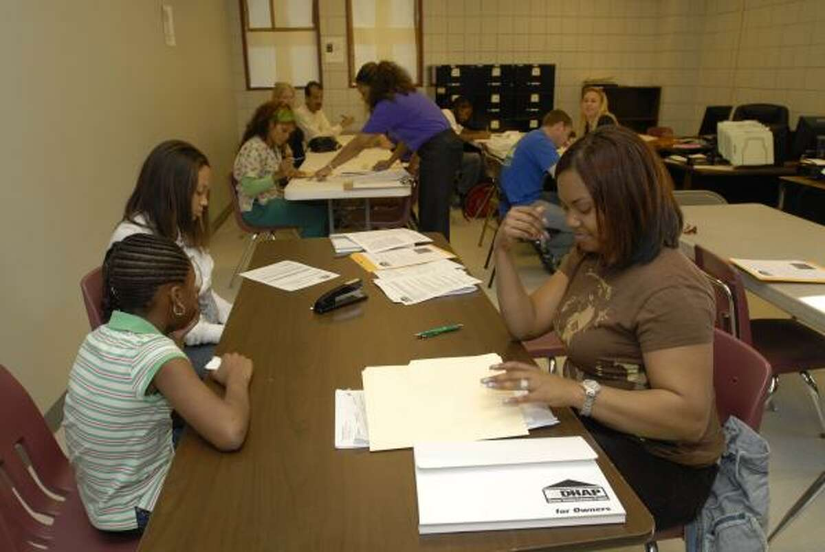 Landlord Carlis Jefferson, right, fills out forms at HUD's Disaster Housing Assistance Program in New Orleans. HUD has asked the Harris County Housing Authority to run the program.