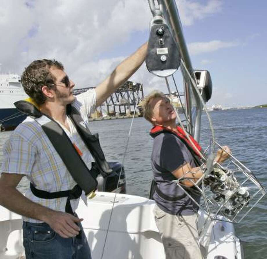 Graduate student Sean Marikle, left, helps Nicholas Perry with a device used to measure oxygen levels in the water off Florida. Photo: WILFREDO LEE, ASSOCIATED PRESS