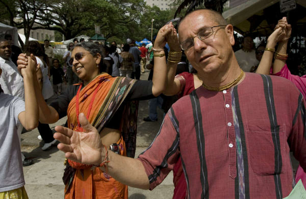 Hansa Medley, left, and Peter Medley, dance and chant with fellow Hare Krishnas at the Houston International Festival.
