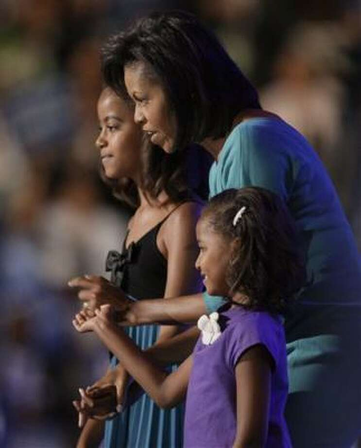 Supporters want the public to see Michelle Obama, shown with her daughters Malia, 10, and Sasha, 7, as a hardworking mother who worked her way to success. Photo: Charlie Neibergall, Associated Press