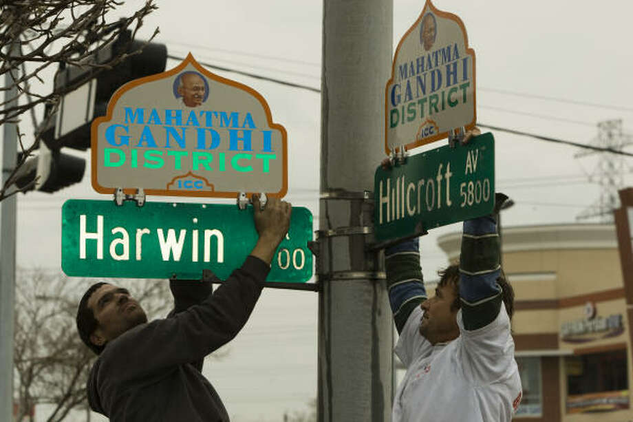 Zane Frazar, left, and Ron Mitchell hang two of 31 new signs that demarcate the Mahatma Gandhi District on Friday. A ceremony is scheduled to inaugurate the new district in the Hillcroft-area neighborhood. Photo: Brett Coomer, Chronicle