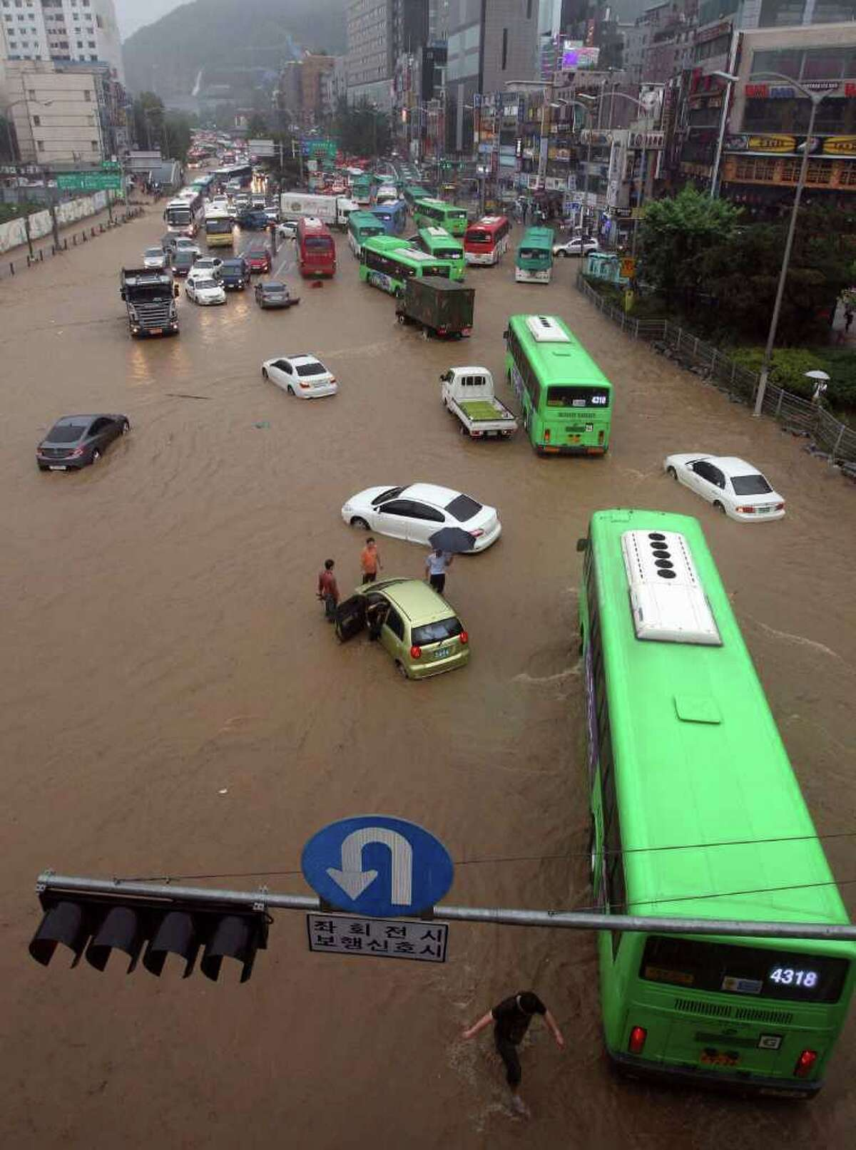 People drive vehicles through a flooded road in Seoul, South Korea, on Wednesday. Heavy rain sent a landslide barreling into a resort in Chuncheon, a northern South Korean town Wednesday. (AP Photo/Lim Hun-jung)