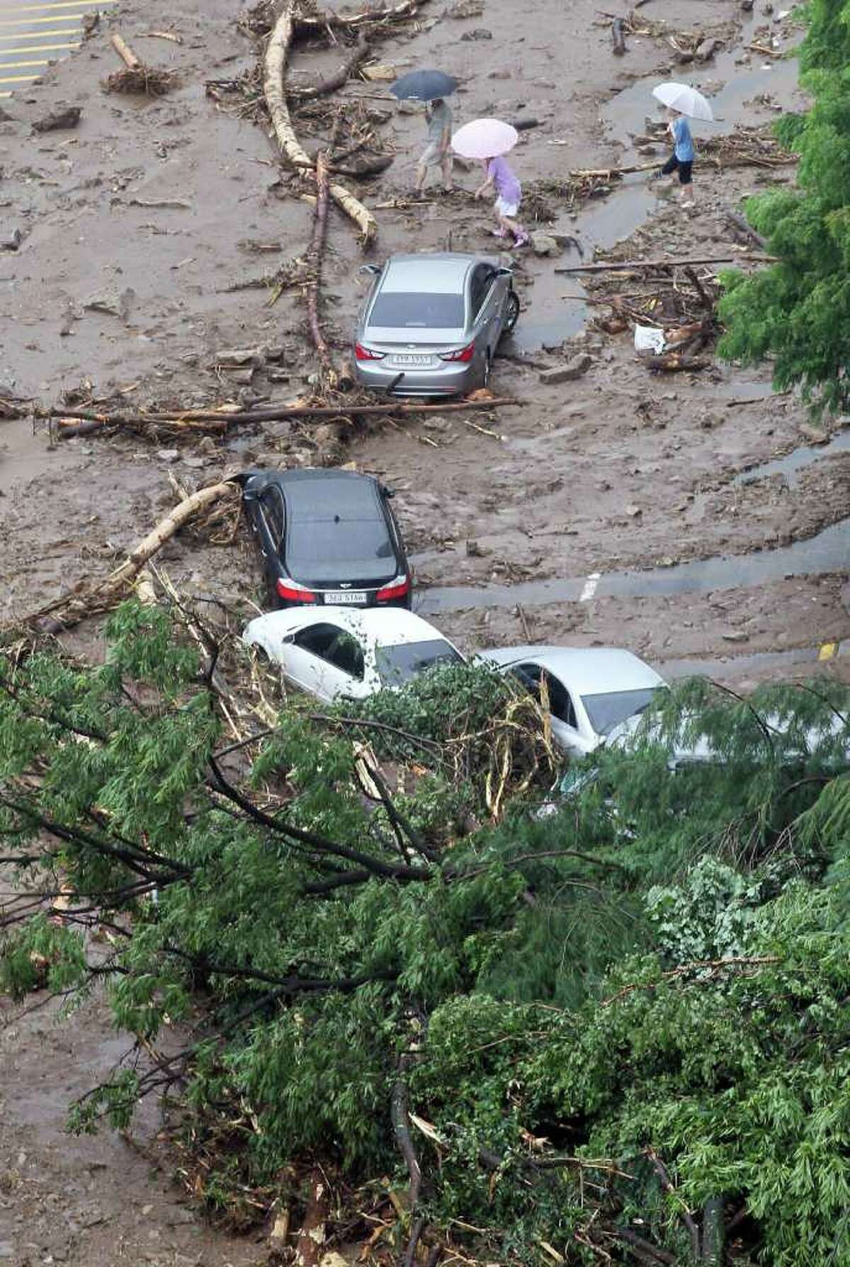 Residents pass by wrecked vehicles after a landslide caused by heavy rains in Seoul, South Korea, on Wednesday. A quick blast of heavy rain sent landslides barreling through South Korea's capital and a northern town Wednesday. (AP Photo/Yonhap, Kim Ju-sung)