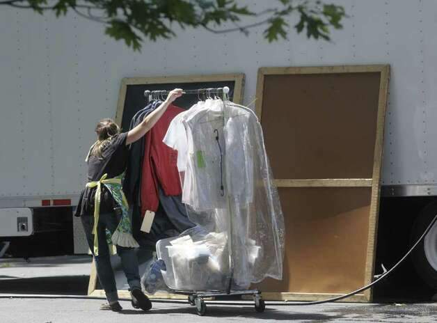 "A crew member on Wednesday wheels a rack of clothing through a parking lot at the Stanford Heights Fire Department in Schenectady. The lot is being used by the crew of the movie ""The Place Beyond the Pines""  while filming is being done nearby. (Paul Buckowski / Times Union) Photo: Paul Buckowski"