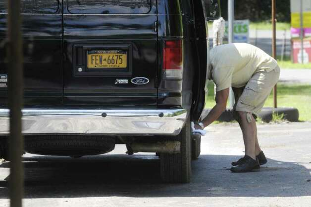 "A van driver on Wednesday wipes down the running board in the parking lot  of the Stanford Heights Fire Department in Schenectady. The lot is being used by the crew of the movie ""The Place Beyond the Pines""  while filming is being done nearby. (Paul Buckowski / Times Union) Photo: Paul Buckowski"
