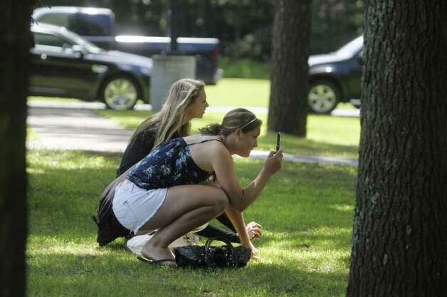 "Friends Erin Kelly, foreground, and Brittany Lee, both from Guilderland, try to get photos of  Ryan Gosling at parking lot that is part of the Stanford Heights Fire Department in Schenectady on Wednesday, July 27, 2011.  The parking lot was being used by the crew of the movie ""The Place Beyond the Pines""  to work out of while filming was being done nearby.   (Paul Buckowski / Times Union) Photo: Paul Buckowski"