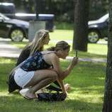 """Friends Erin Kelly, foreground, and Brittany Lee, both from Guilderland, try to get photos of  Ryan Gosling at parking lot that is part of the Stanford Heights Fire Department in Schenectady on Wednesday, July 27, 2011.  The parking lot was being used by the crew of the movie """"The Place Beyond the Pines""""  to work out of while filming was being done nearby.   (Paul Buckowski / Times Union)"""