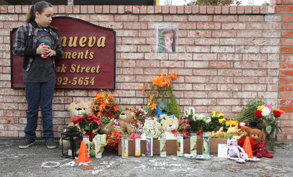 Jennifer Zamora, 11, visits a makeshift memorial to Jonathan Foster on Thursday outside the Villanueva Apartments, where the 12-year-old lived and was last seen.