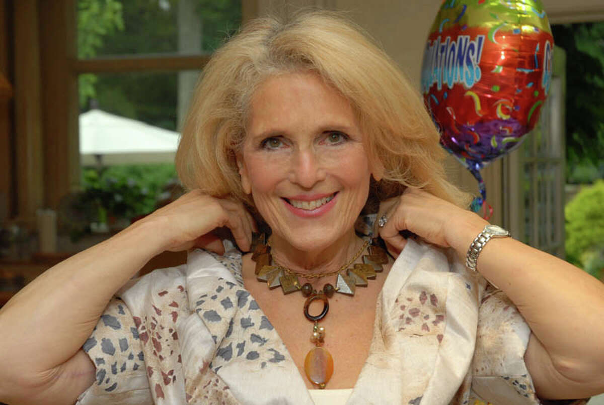 Pam Friedlander, of Positive Reflections, displays a necklace in her collection of accessories during a celebration of her fifth year in business.