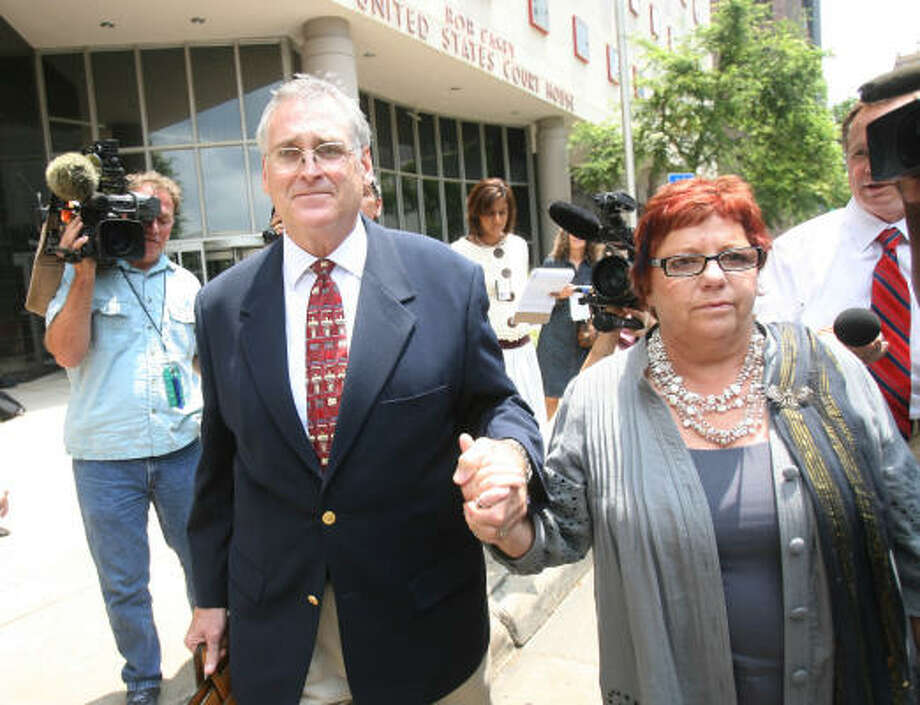 U.S. District Judge Samuel Kent holds his wife's hand as she walks away from the Bob Casey Federal Court House after being sentenced 33 months behind bars. Photo: Mayra Beltran, Chronicle