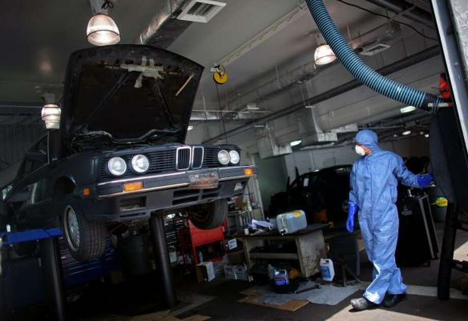 "Nick Clites prepares to disable a BMW's engine at DCH Paramus Honda in Paramus, N.J.  The federal government, in its ""cash for clunkers"" program, requires vehicles to be put totally out of service before it will process the reimbursement claims. Photo: YANA PASKOVA, NYT"