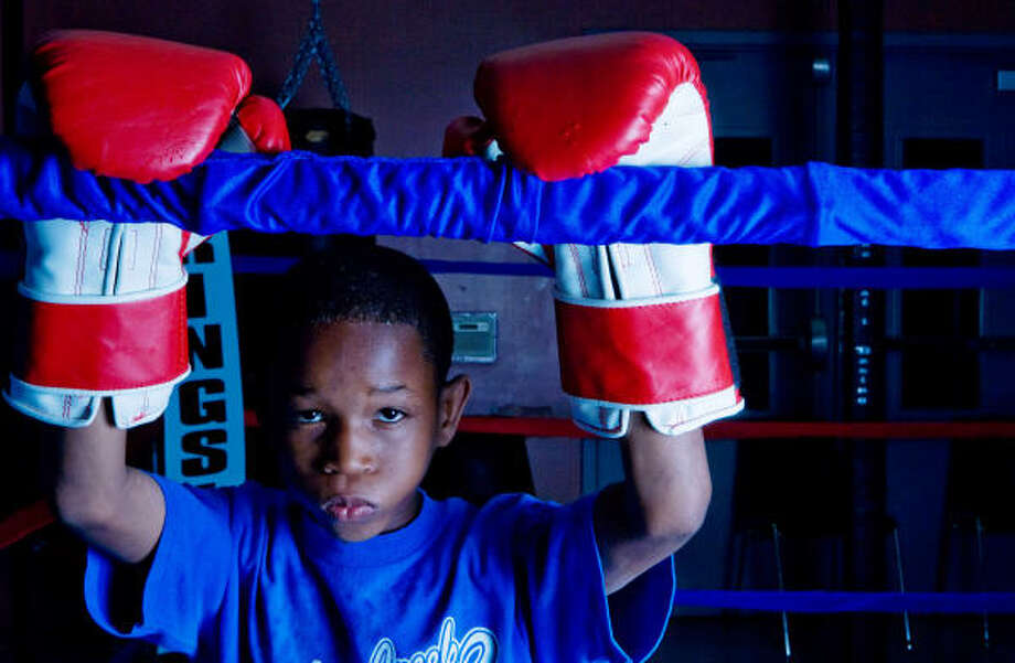 KID, GLOVES: David Williams is all focus and concentration at Cuney Homes Community Center, where he is learning to box under Martin. Photo: Billy Smith II, Chronicle