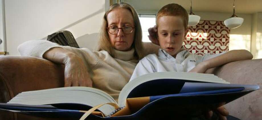 Karen Baughn and her son, Nash, 12, look at The Golden Compass. The Annunciation Orthodox School sixth-grader and his mom started the novel after controversy over its possible removal. Photo: JOHNNY HANSON, CHRONICLE
