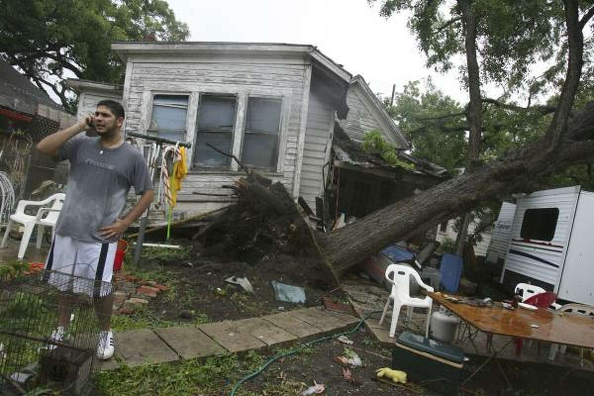 Nicolas Fraga phones relatives about damage done to his home after a suspected tornado spawned by outflows from the remnants of Hurricane Dolly swept through San Antonio on Thursday. The storm uprooted a trees and damaged houses.