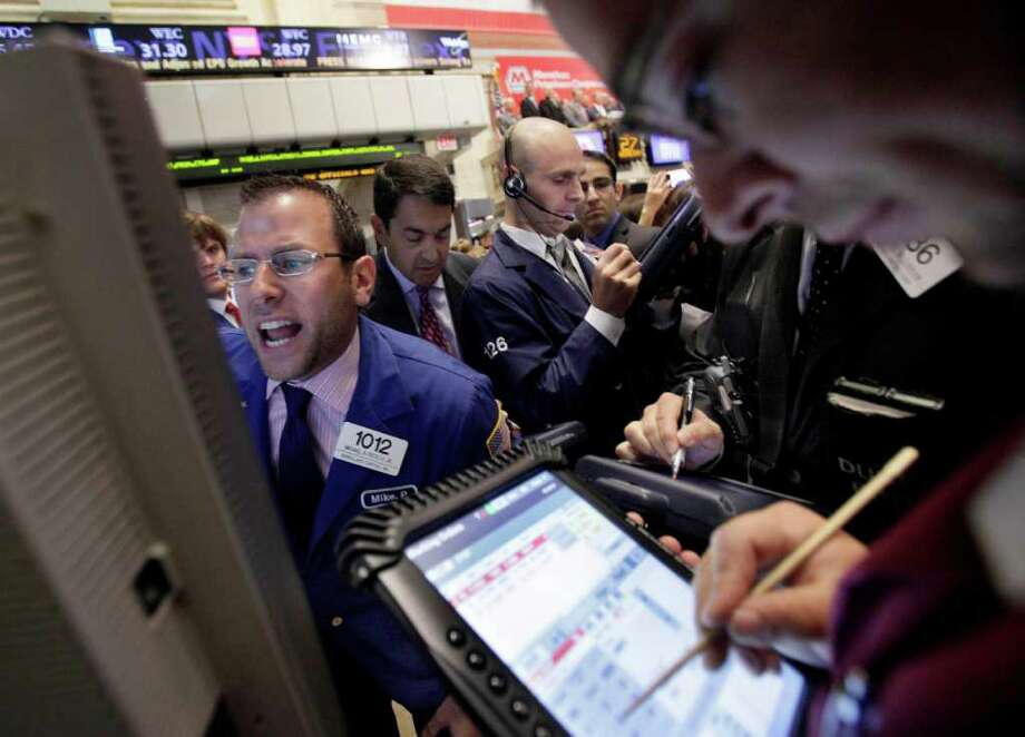 Specialist Michael Pistillo, left, calls out prices as he works at his post on the floor of the New York Stock Exchange Wednesday, July 27, 2011. (AP Photo/Richard Drew) Photo: Richard Drew, STF / AP