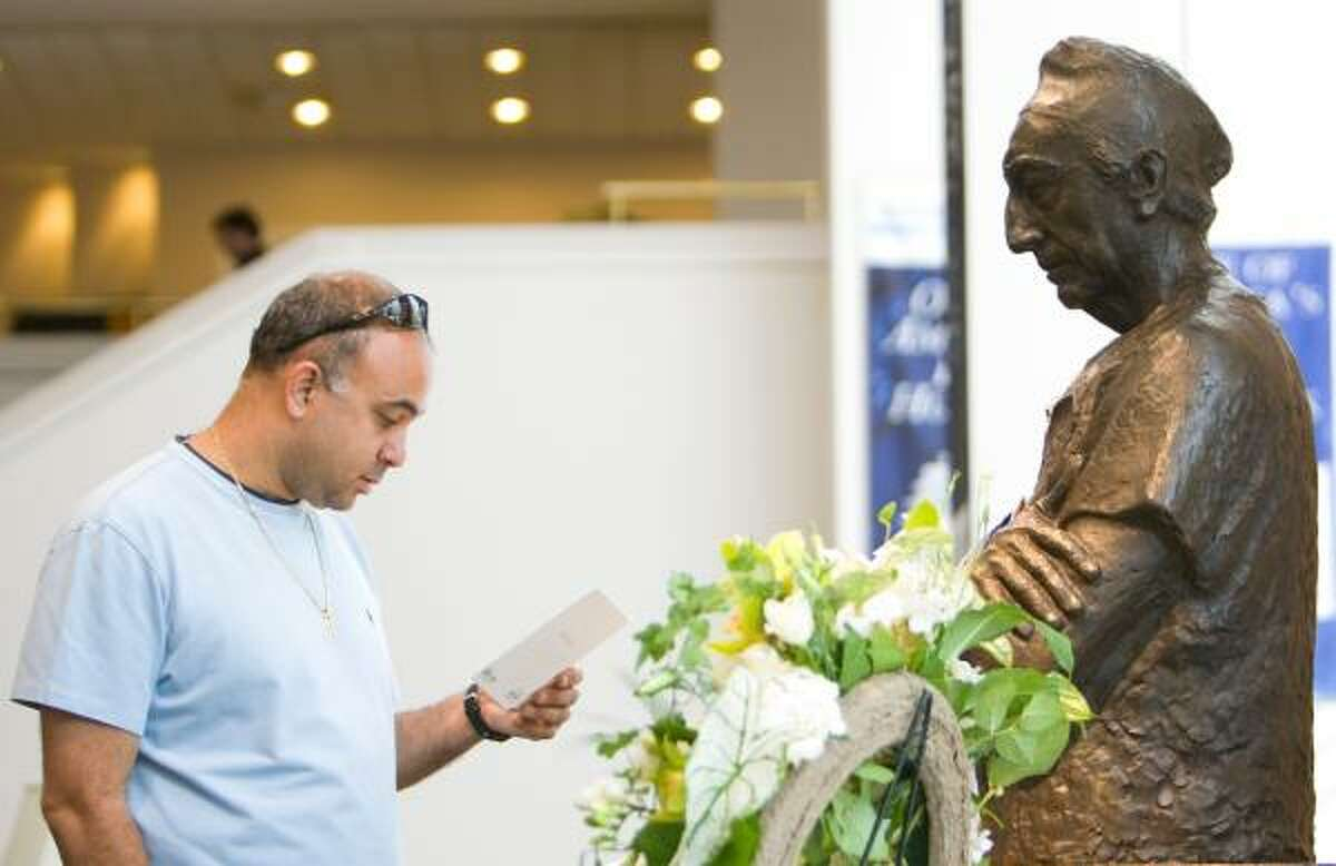 Tony Nabbout of Houston reads a card Sunday left by a memorial book in the lobby of The Methodist Hospital.