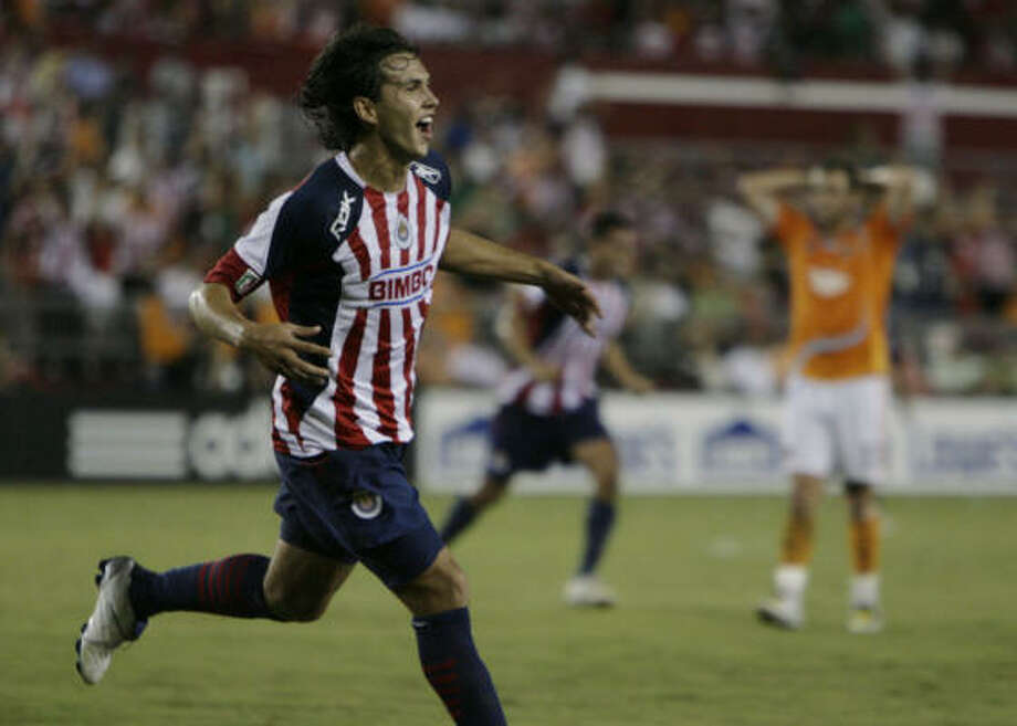 Mexican soccer team Chivas De Guadalajara's Omar Arellano celebrates a goal as the Dynamo's Brad Davis is seen dejected in the background in the second half of a SuperLiga Tournament game on Tuesday in Houston. SuperLiga, which is on its second year, is an annual tournament that features four teams from the Mexican Soccer League and four from the U.S. MLS league. Photo: Julio Cortez, Chronicle