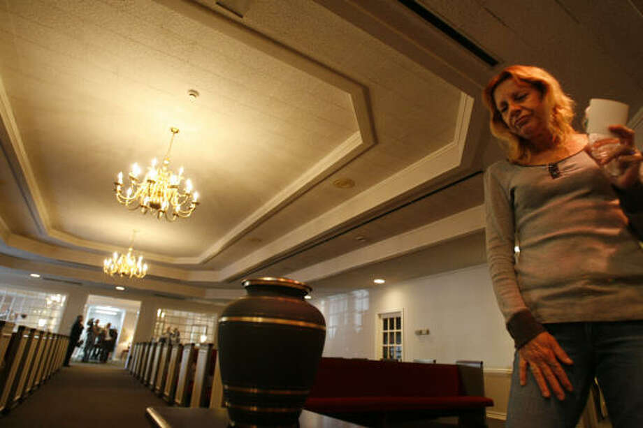 Lenore McNiel pauses near the urn holding the ashes of her brother, Randell Lee Harvey, after his funeral at Earthman Funeral Home on Saturday in Houston. Photo: Sharon Steinmann, Chronicle